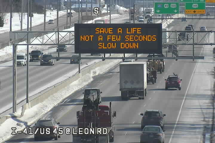 """A digital traffic sign over a highway reads """"Save a Life Not a Few Seconds Slow Down."""""""