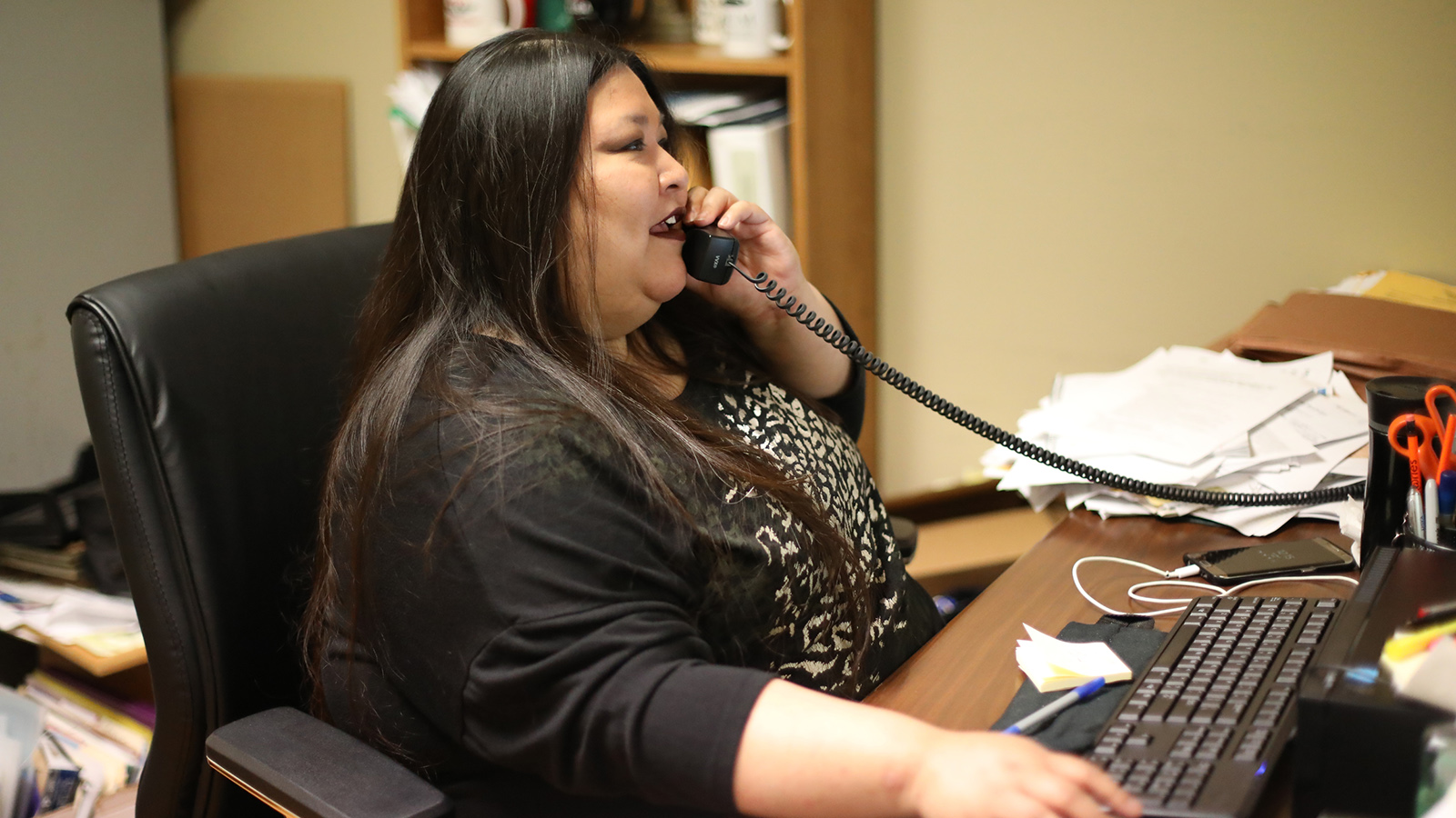Janie Ocejo speaks on phone at desk