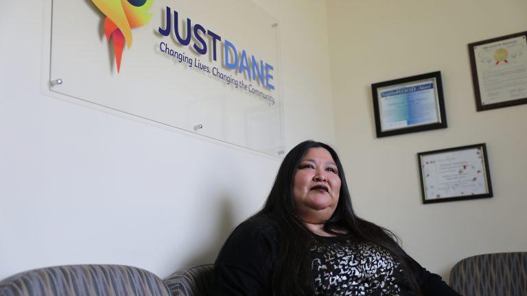 Janie Ocejo sits under a JustDane office sign