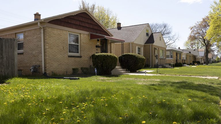Front entrances of houses along street with lawns and trees in the front yards.