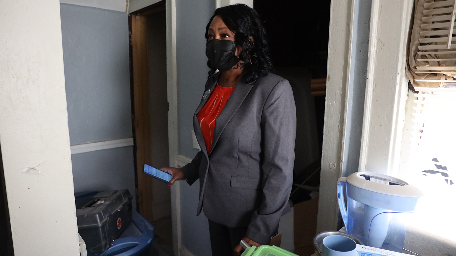 An individual wearing a face mask stands inside a house for sale.