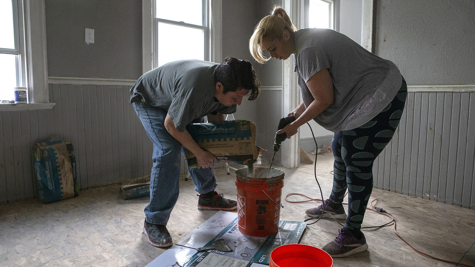 Two people prepare concrete for tiling inside room of a house being renovated