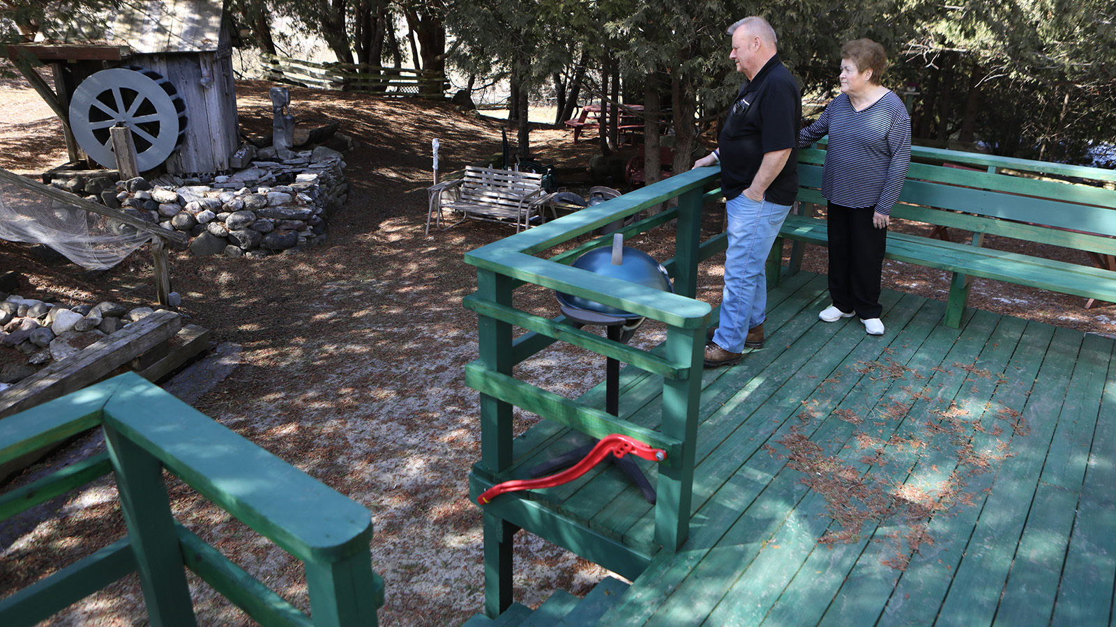 Two people stand on a deck and look at a well in their backyard.