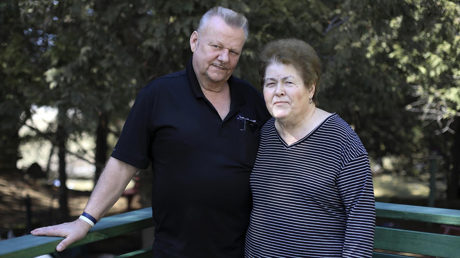Portrait of two people standing in backyard deck.