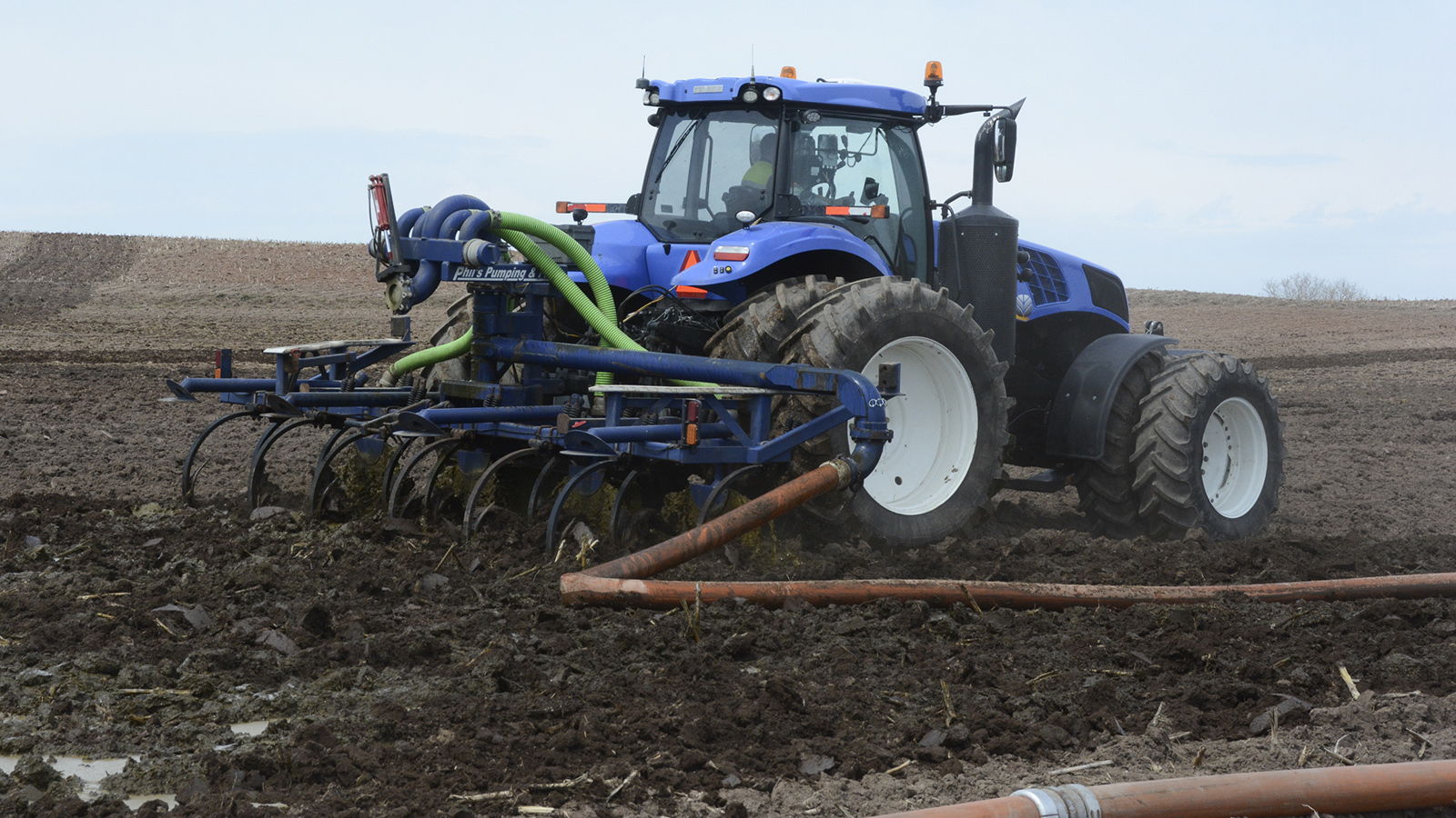 A tractor spreads manure on an open farm field.