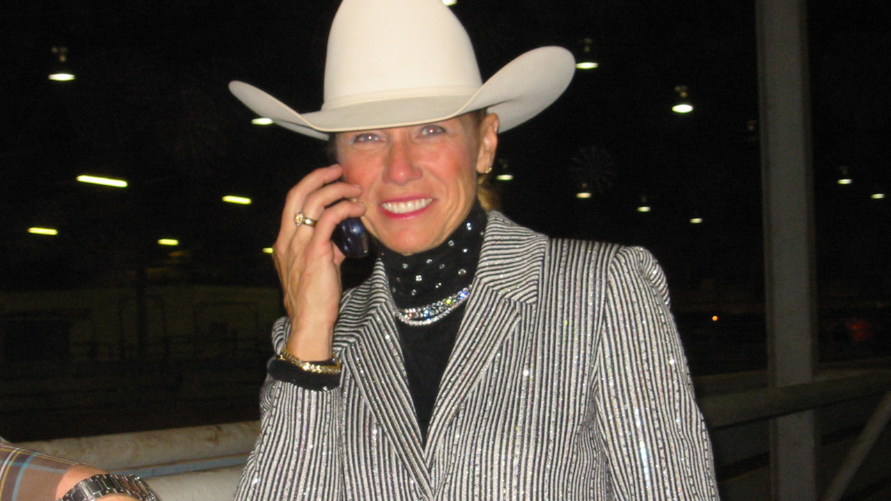 A woman wearing a cowboy hat smiles at the camera