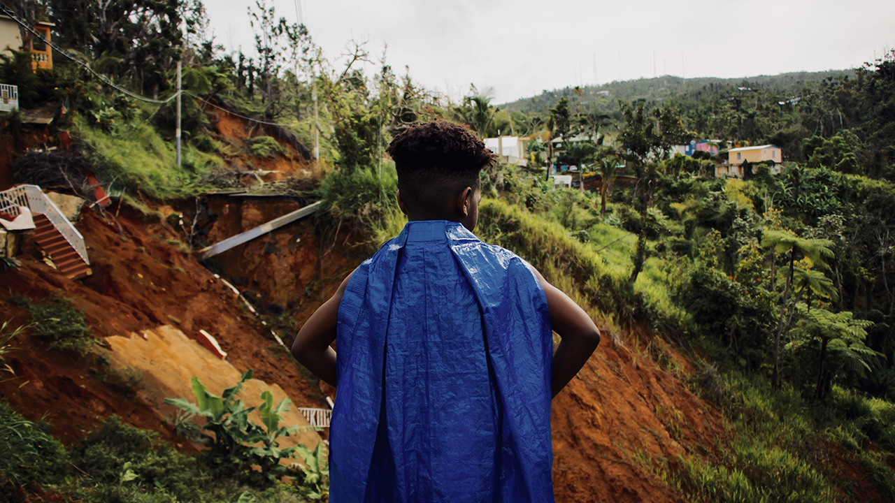 A boy wearing a blue tarp as a cape stands with his back to the camera.
