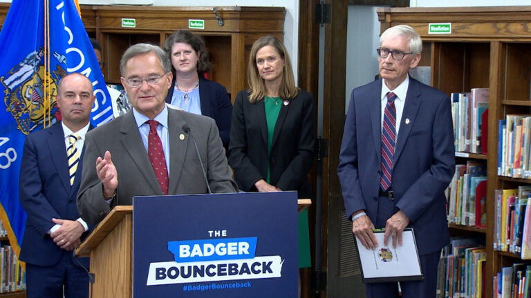 Peter Barca standing at podium in school library surrounded by Tony Evers and other members of the governor's administration