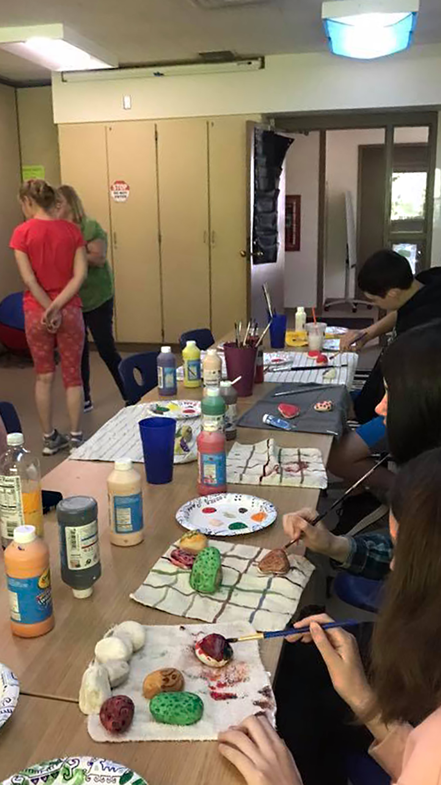 Students sit at a table painting inside a classroom
