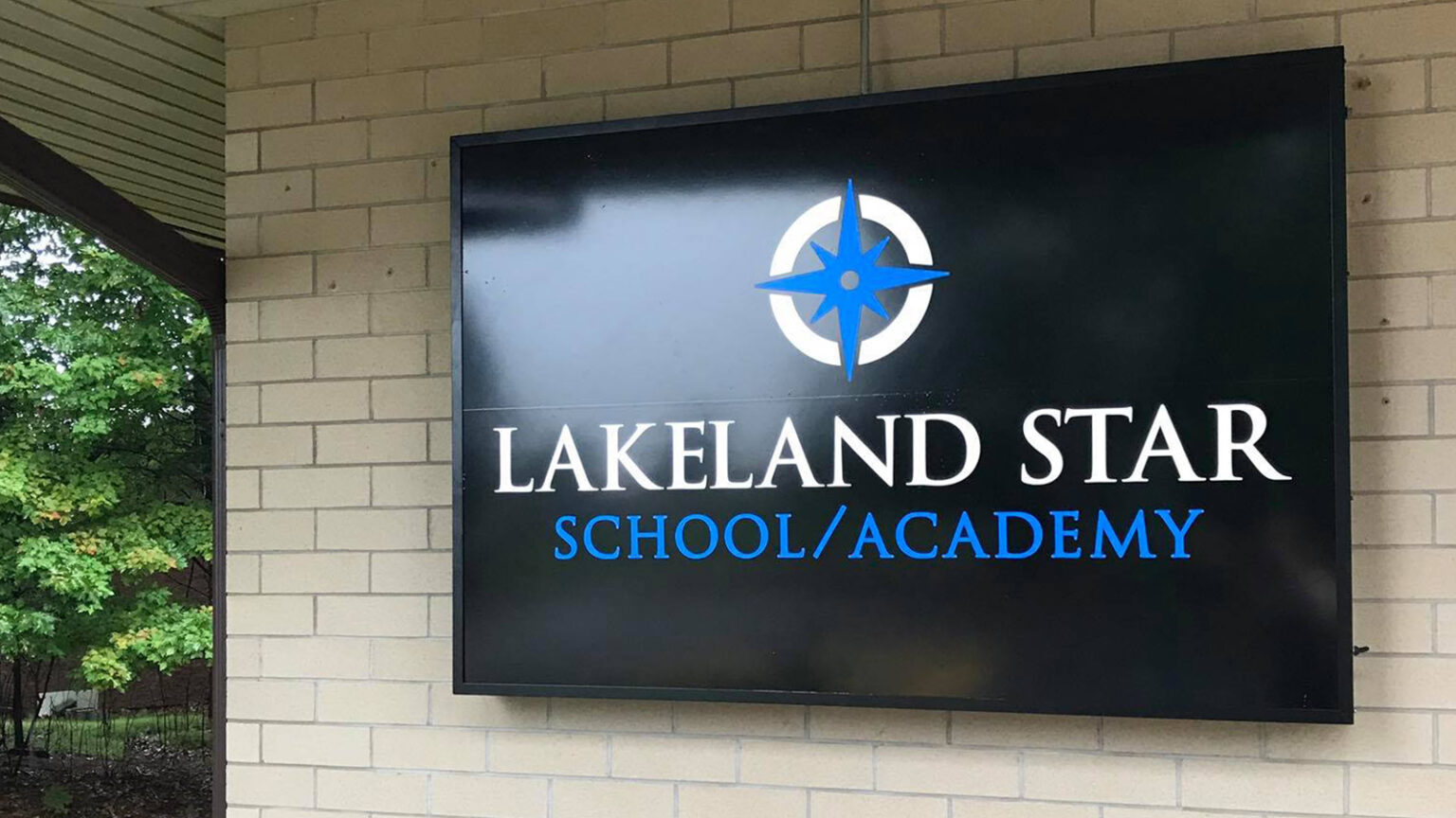 A sign for Lakeland STAR School/Academy on an exterior brick wall