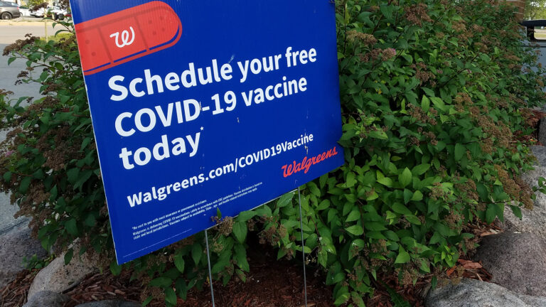 A yard sign next to bushes reads Schedule your free COVID-19 vaccine today with a Walgreens URL.