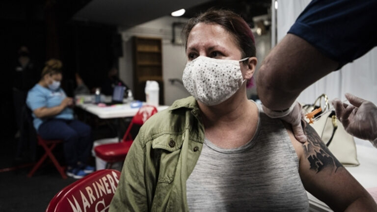 A woman wears a face mask as she receives a COVID-19 vaccine