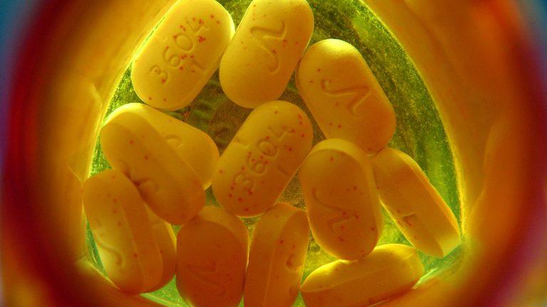 A dozen pills sit at the bottom of an orange prescription medication container.