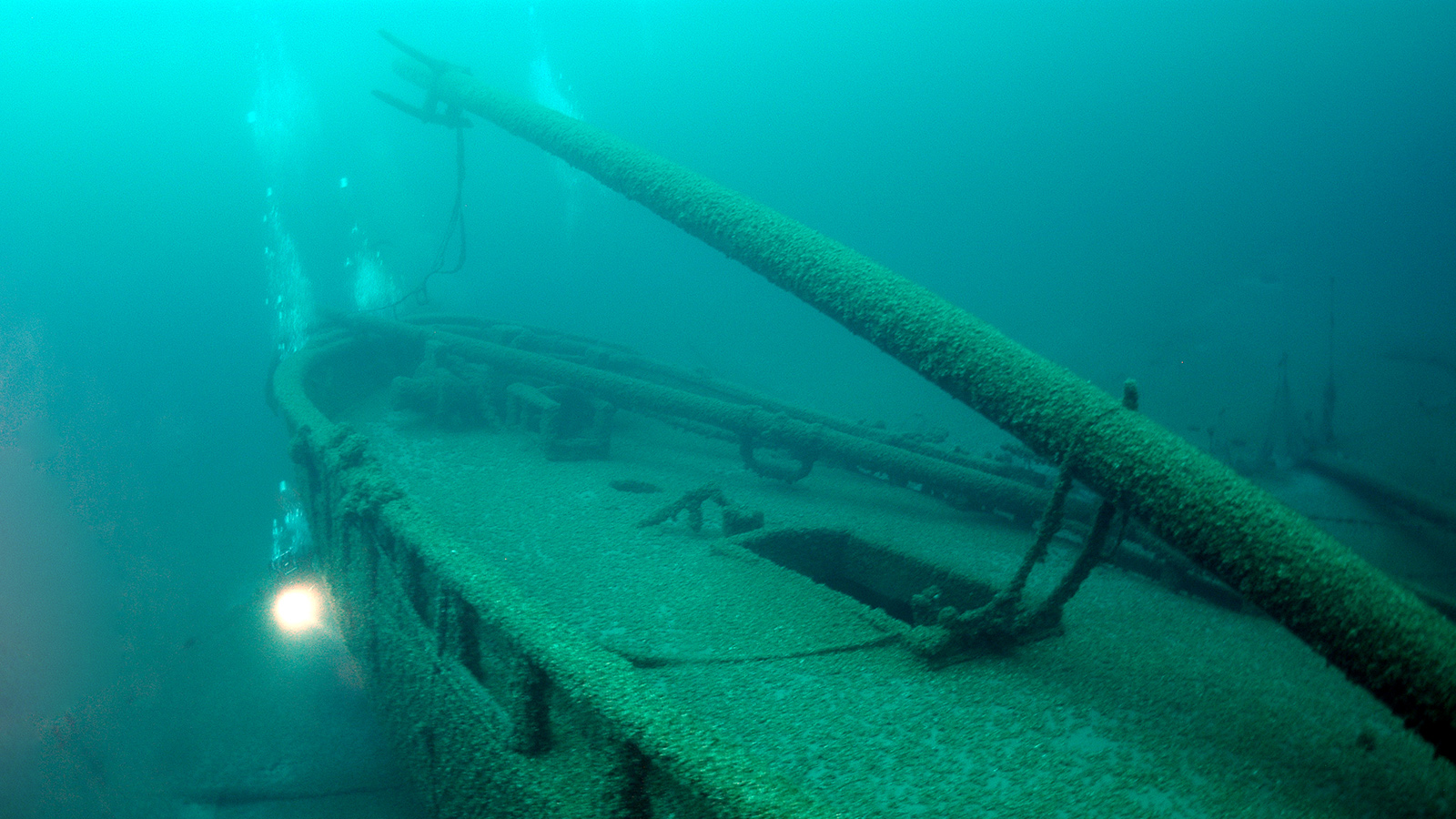 Underwater photo of diver exploring the lower hull of a shipwreck