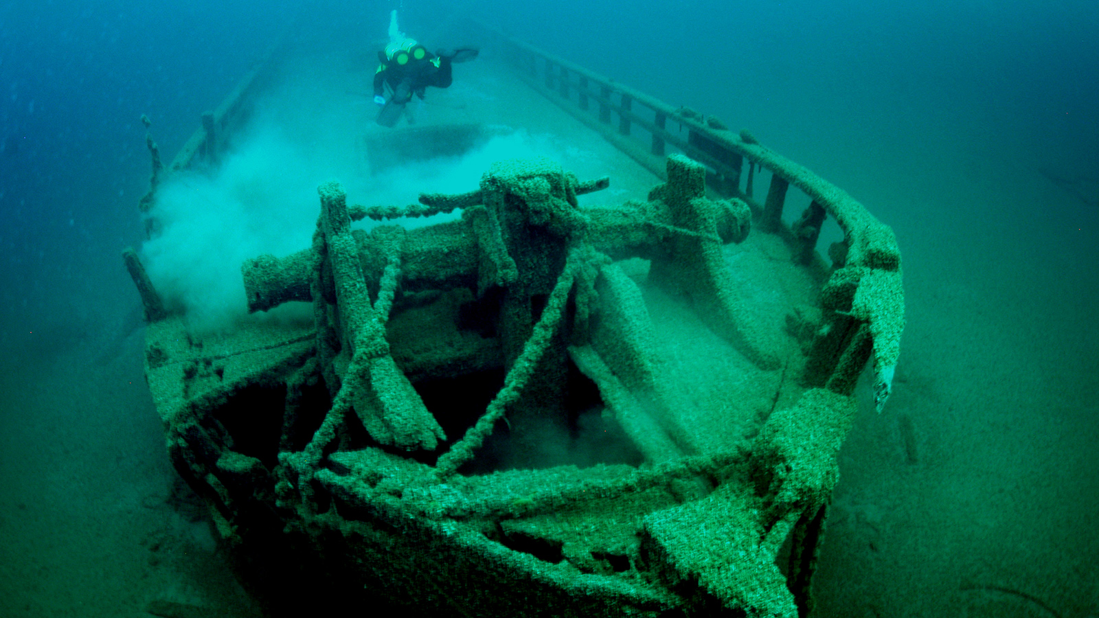 Underwater photo of diver looking down at the deck of a shipwreck
