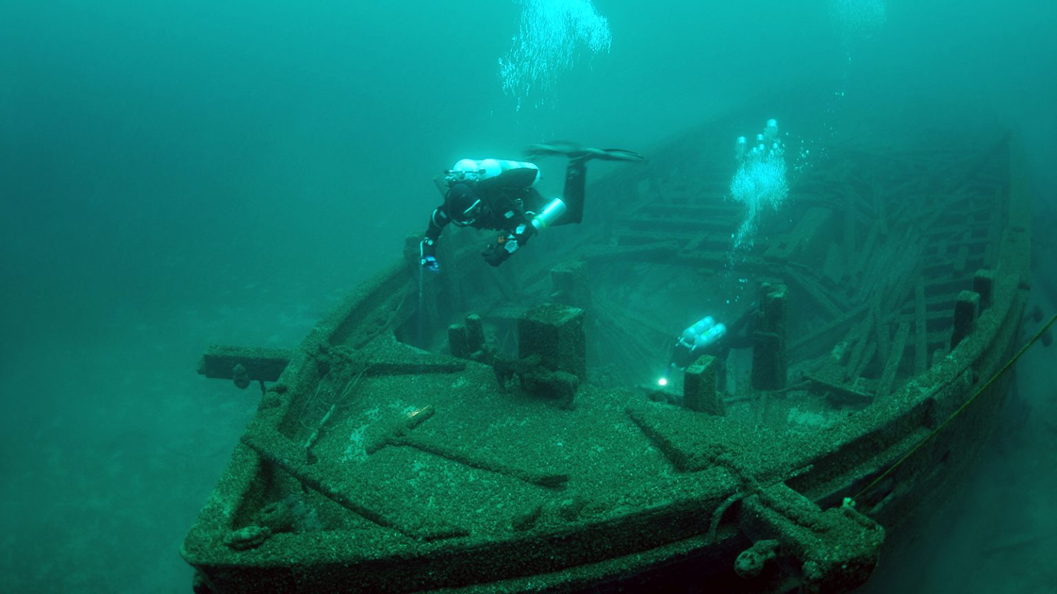 Underwater photo of divers looking down at a shipwreck