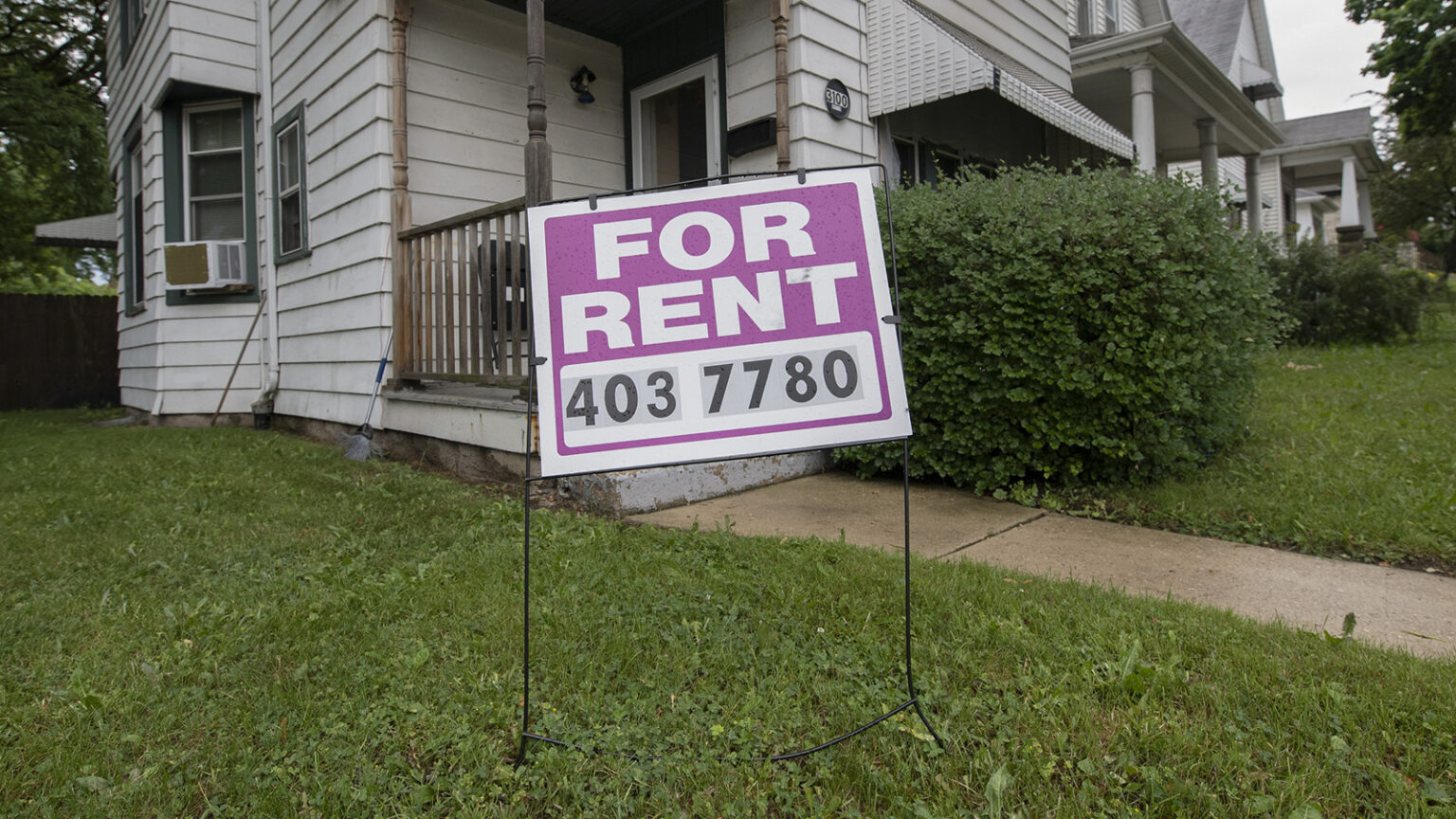 A For Rent sign in front the porch and entrance to a house