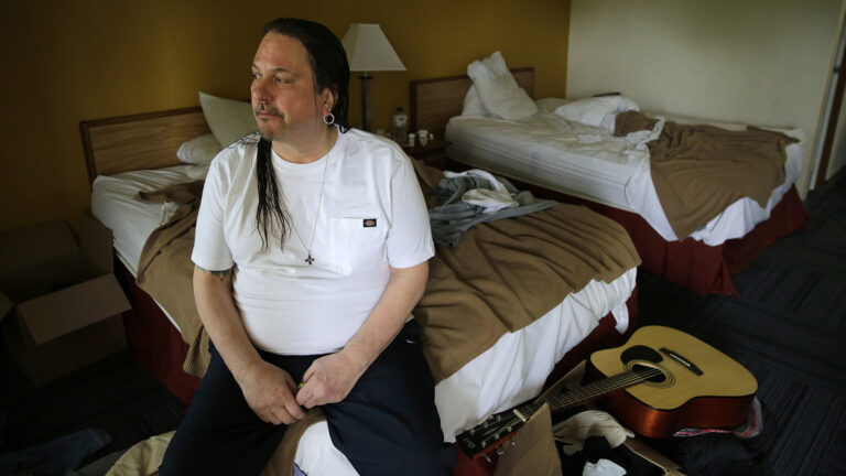 Christopher Kartsounes sitting on a bed in his room at an inn in Appleton, Wisconsin.