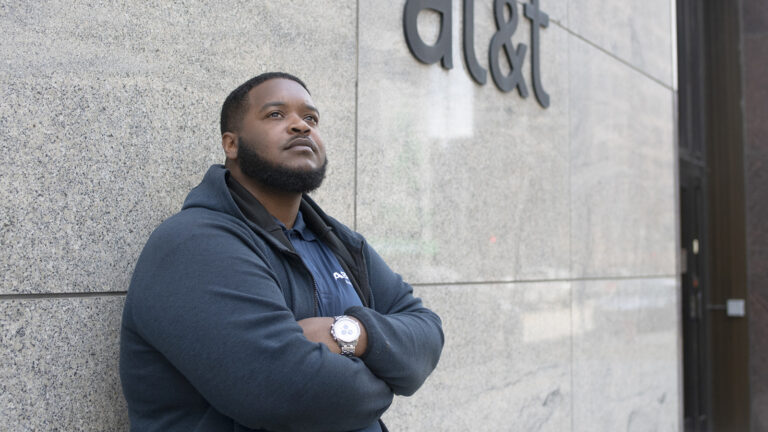 James Rudd standing in front of building with marble panels and AT&T logo