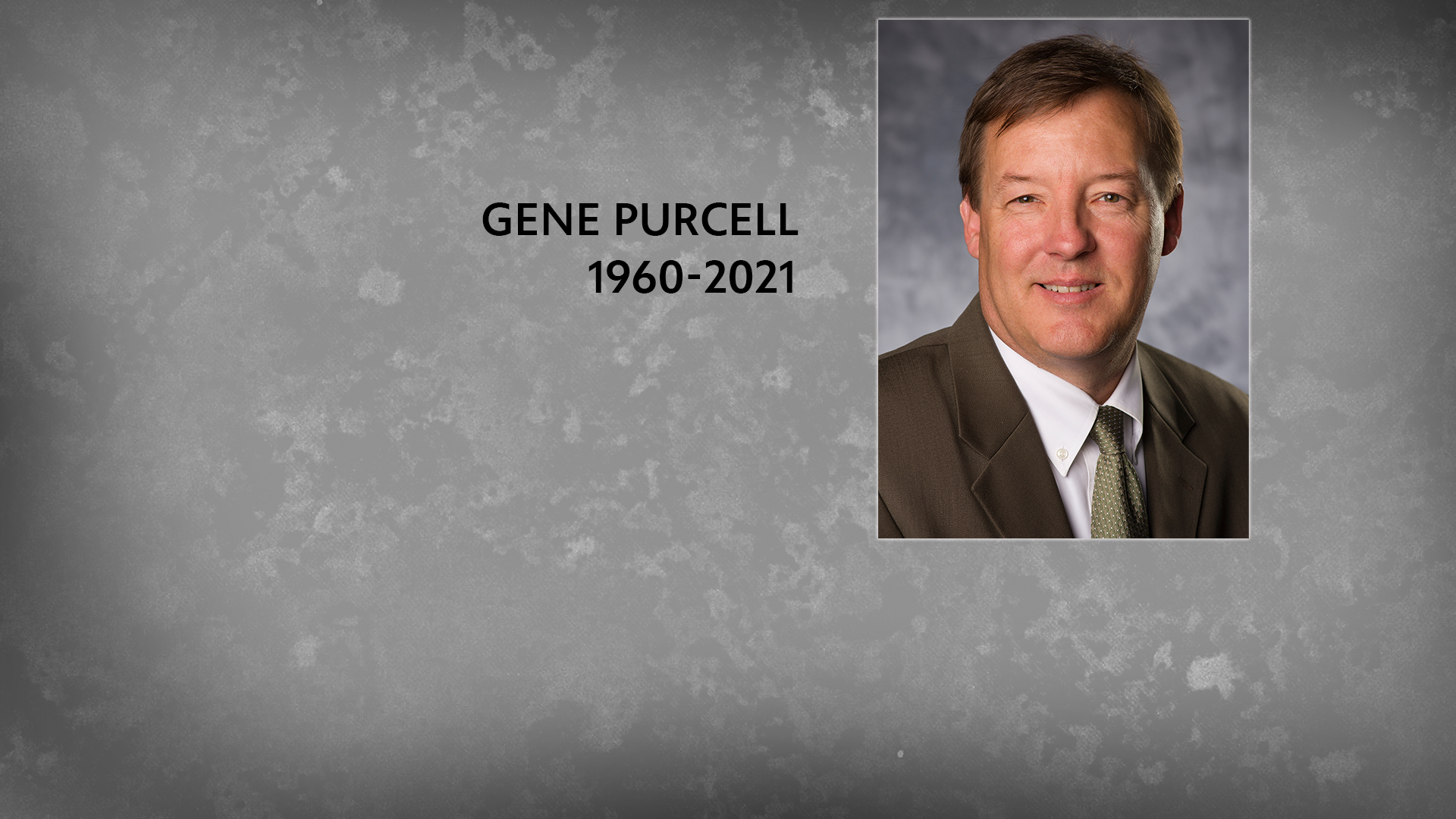 """A portrait of Gene Purcell overlaying a plain grey background with """"Gene Purcell (1960-2021) in black text"""