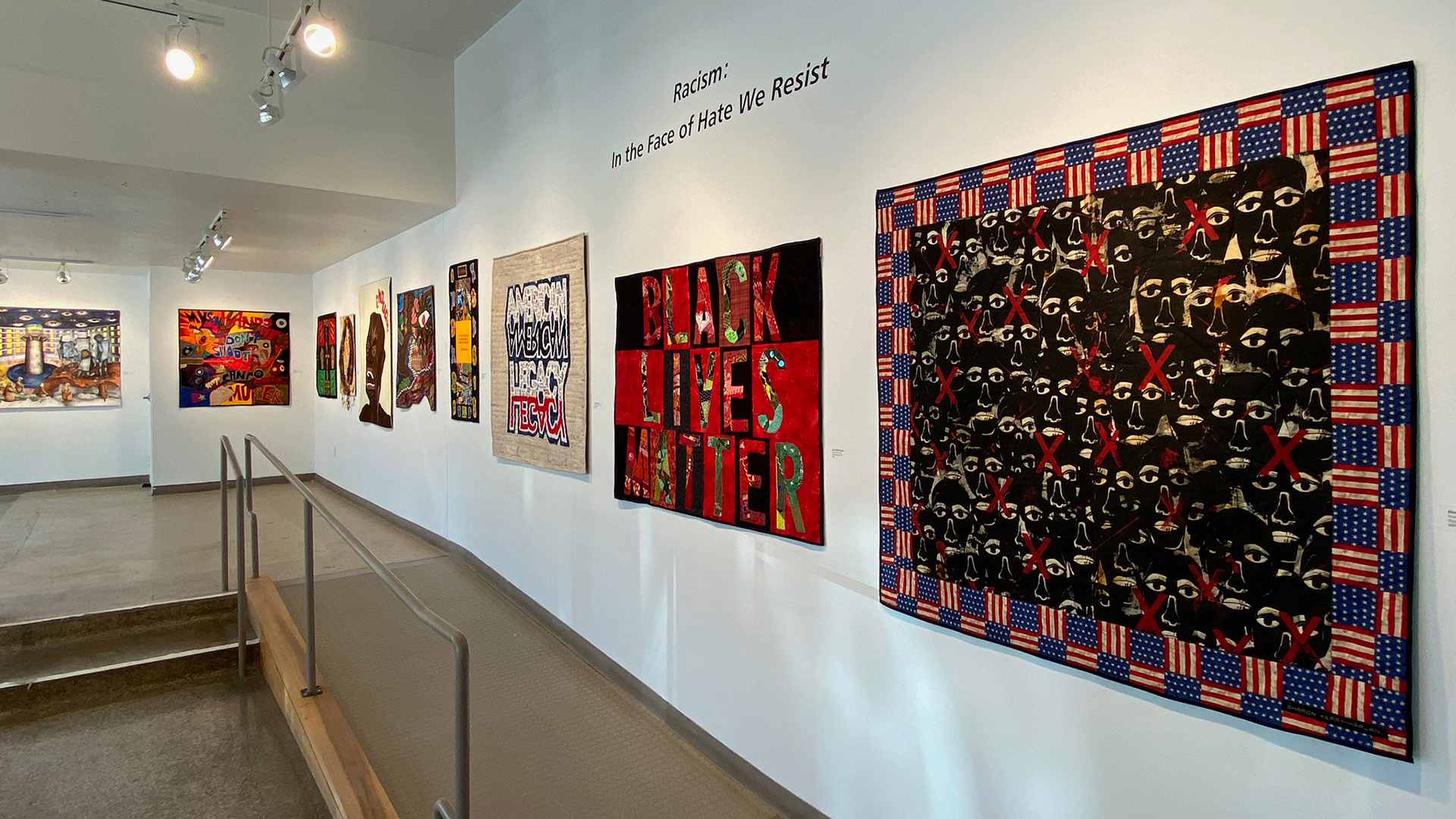 Quilts hanging on the walls of an art gallery