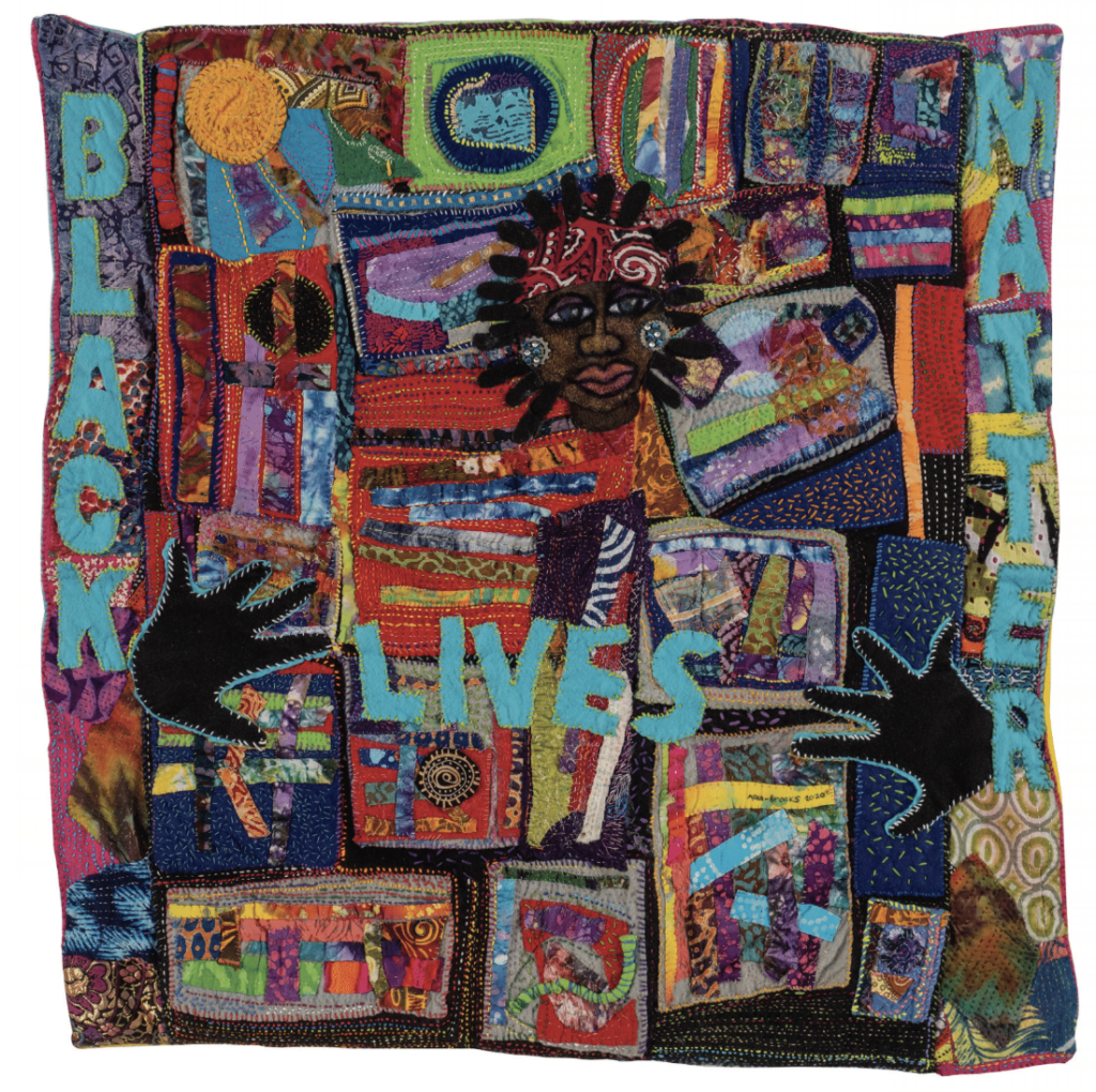 """A colorful quilt featuring a Black woman's face and hands with the words """"Black Lives Matter"""""""