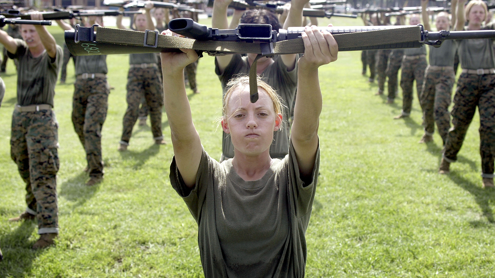 A female marine in combat training holds a gun up.