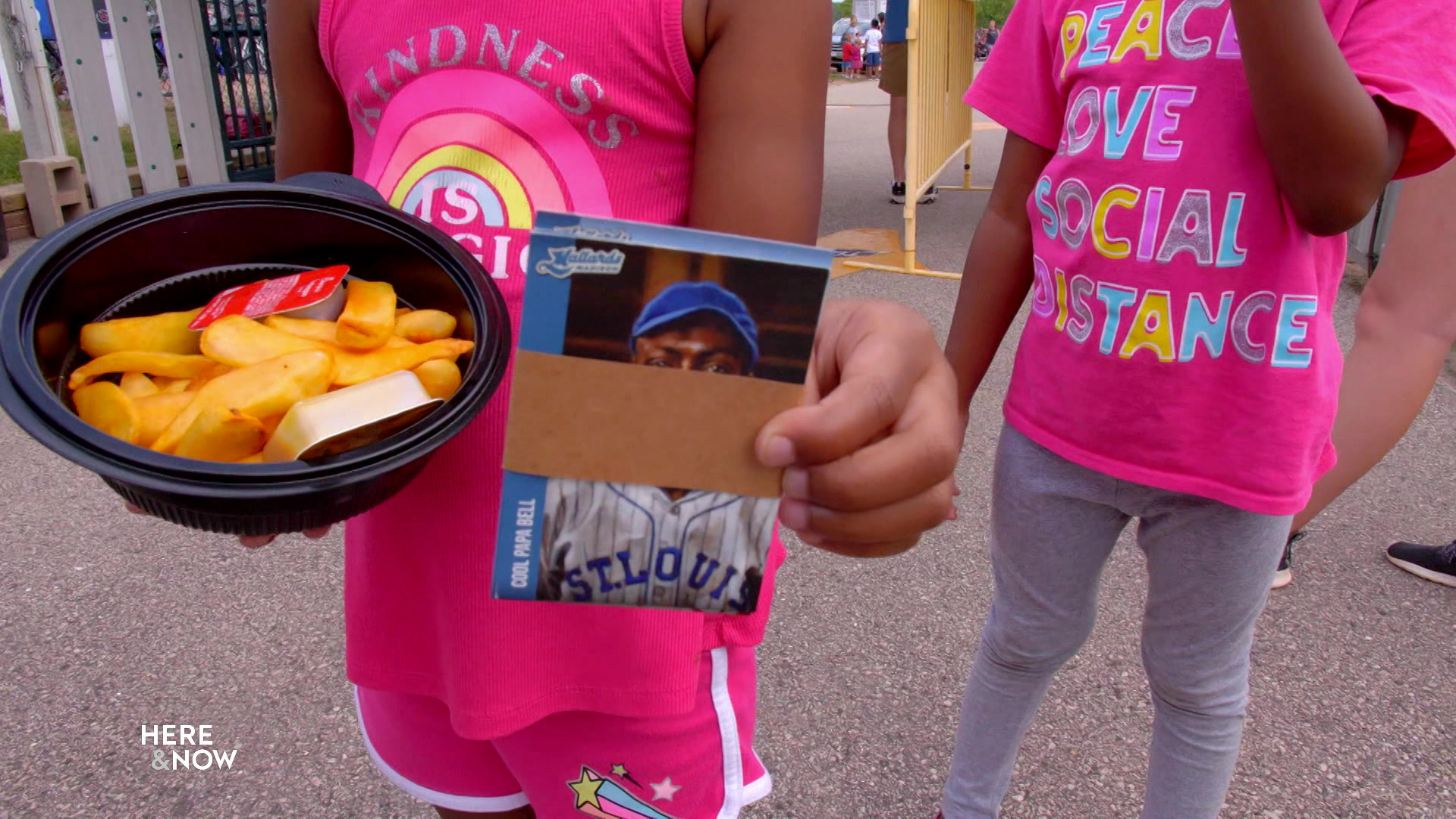 A young baseball fan hold Madison Mallards promotional baseball cards for Negro Leagues players.