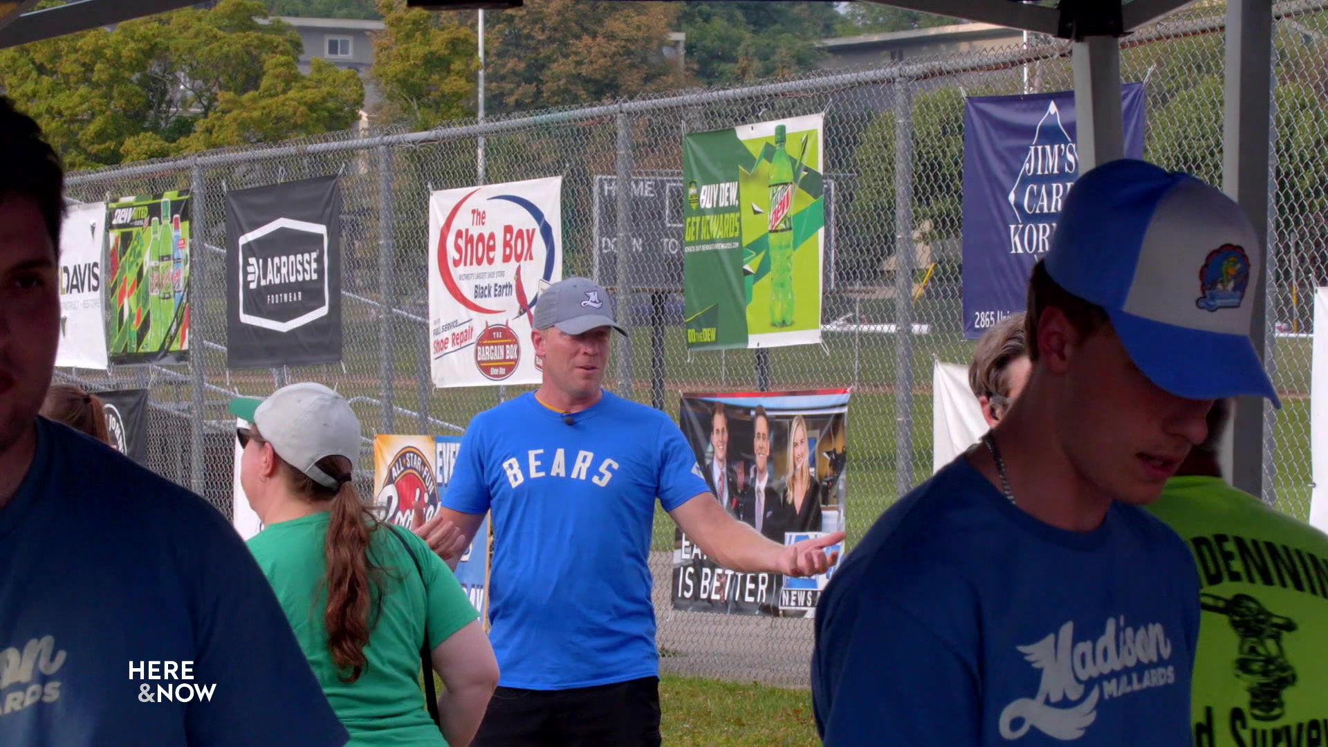 Vern Stenman stands near the entrance to the Duck Pond in front of a fence with advertisements.