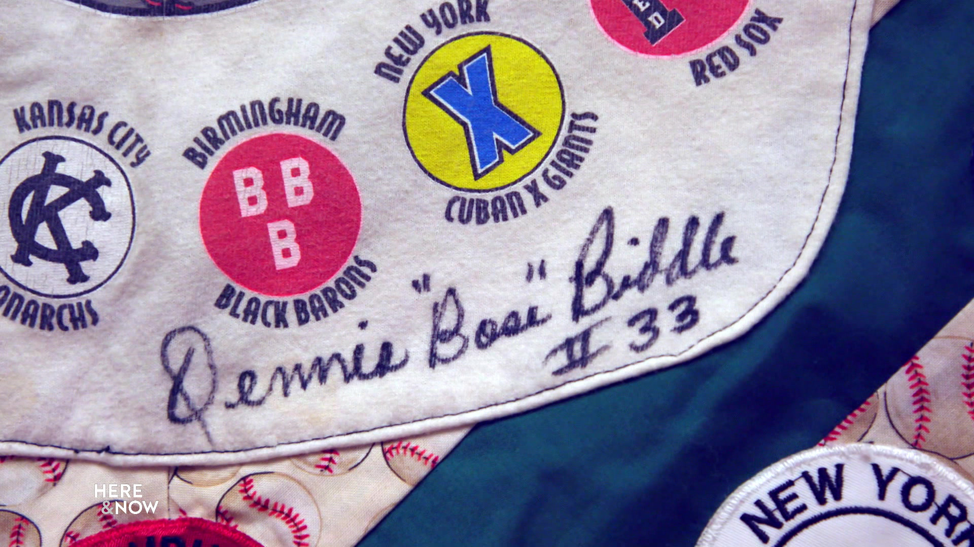 """The autograph of Dennis """"Boss"""" Biddle #33 appears next to the logos of Negro Leagues baseball teams on a quilt commemorating their history."""