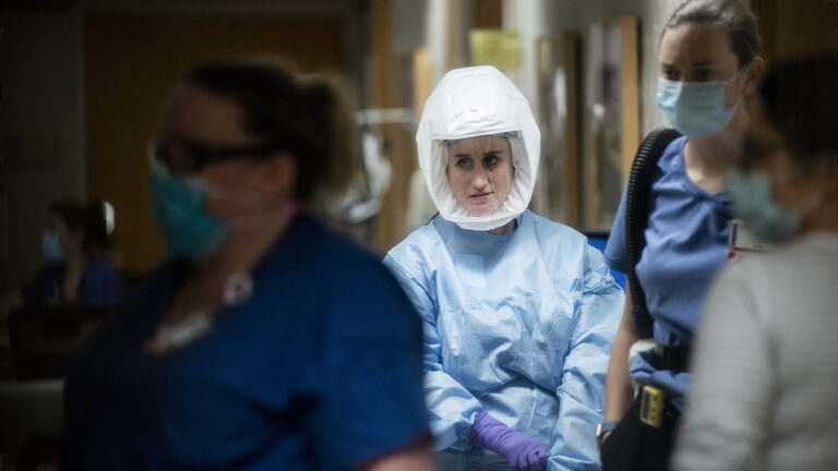 Nurses and doctors wearing personal protective equipment walk through a hallway.