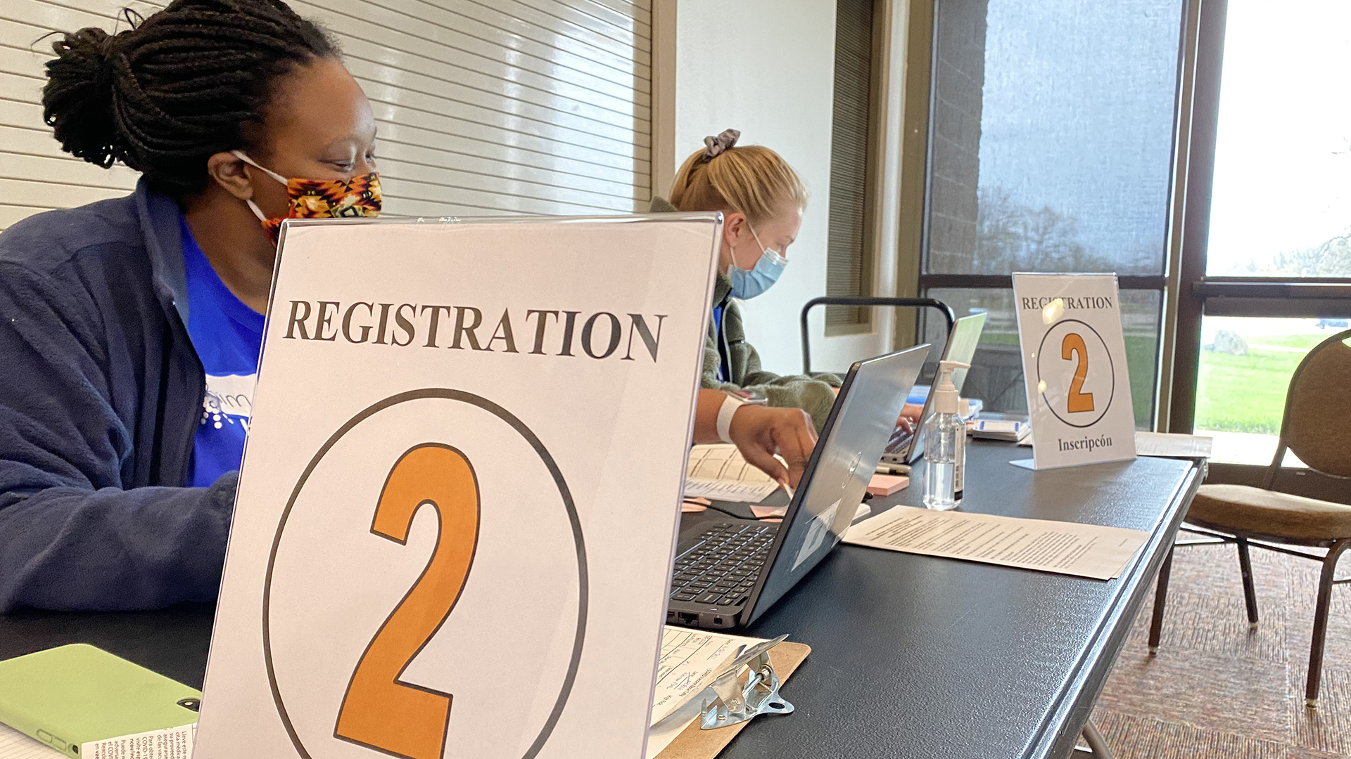 Public Health Madison & Dane County staff work at a vaccination clinic registration table .
