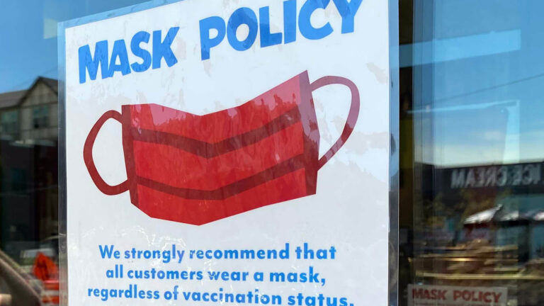 A sign on a door reads Mask Policy: We strongly recomment that all customers wear a mask, regardless of vacciation status.