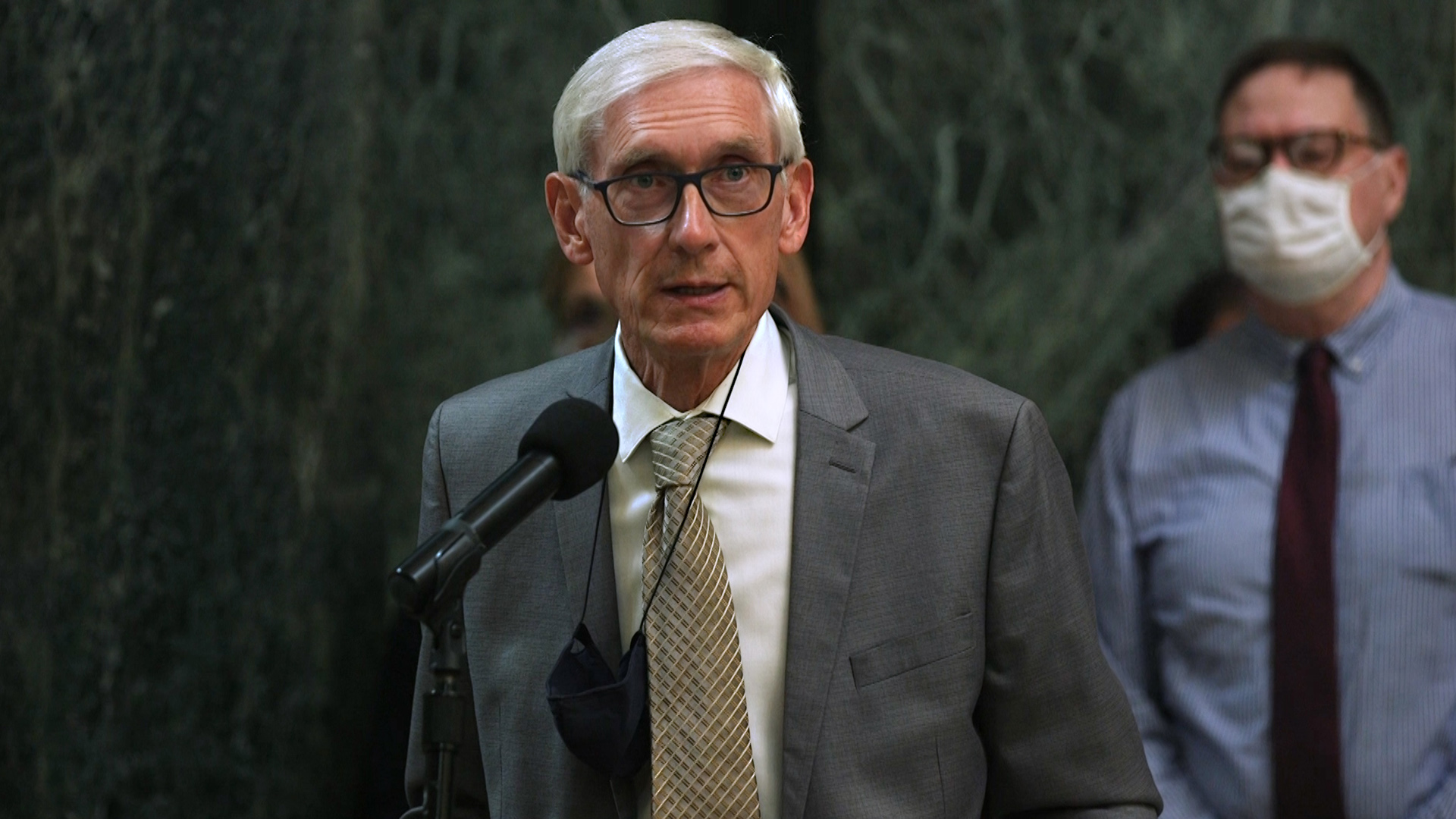 Tony Evers speaks at a microphone in the Wisconsin Capitol.