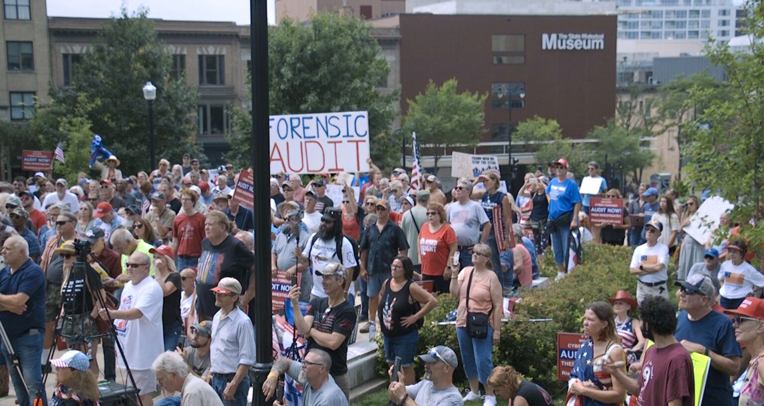 Protestors gather in front of the State Street entrance of th Wisconsin Capitol, with one holding a sign reading Forensic Audit.