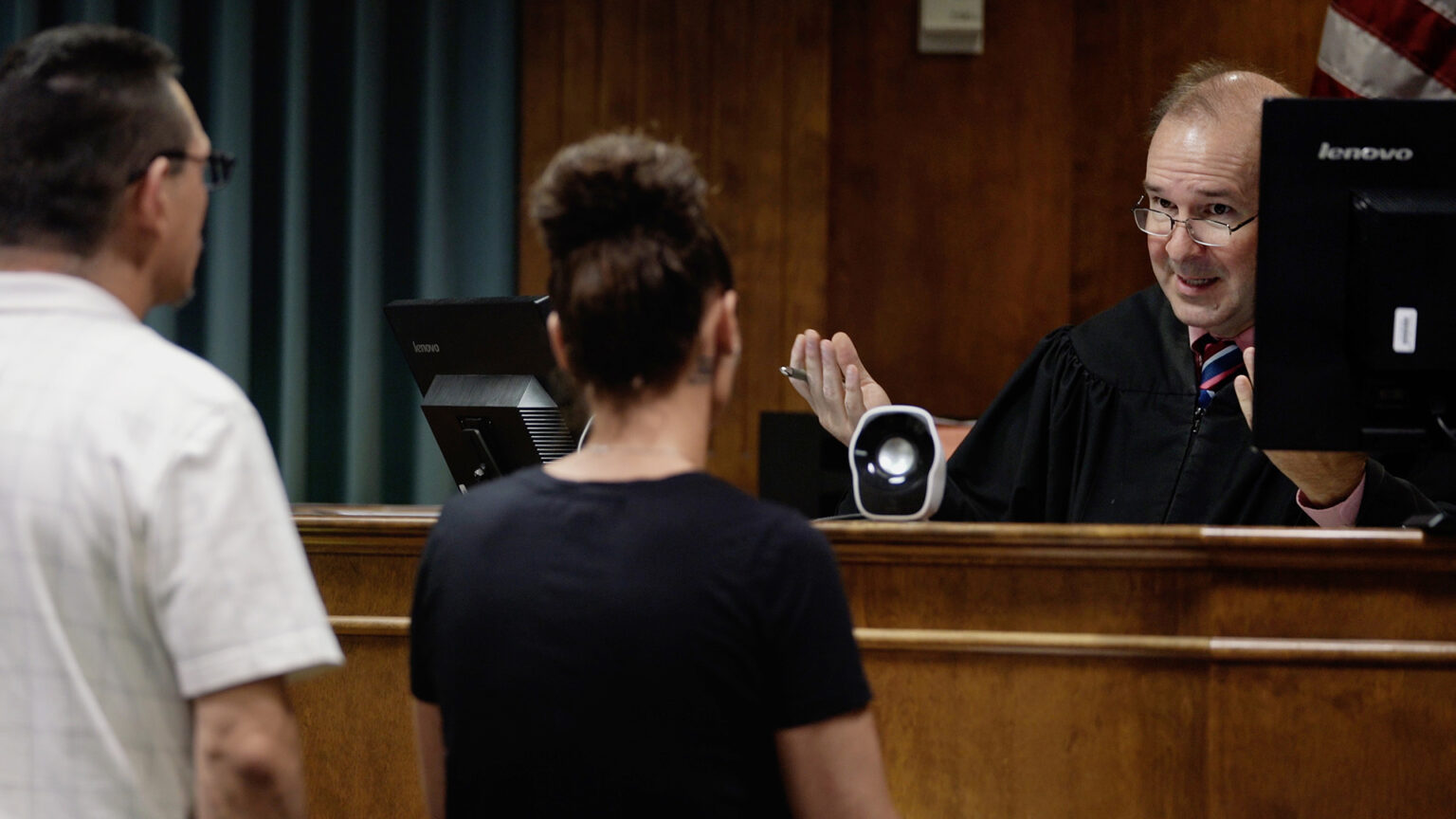 Paul Burke sits at a raised judge's bench and speaks in an eviction proceeding