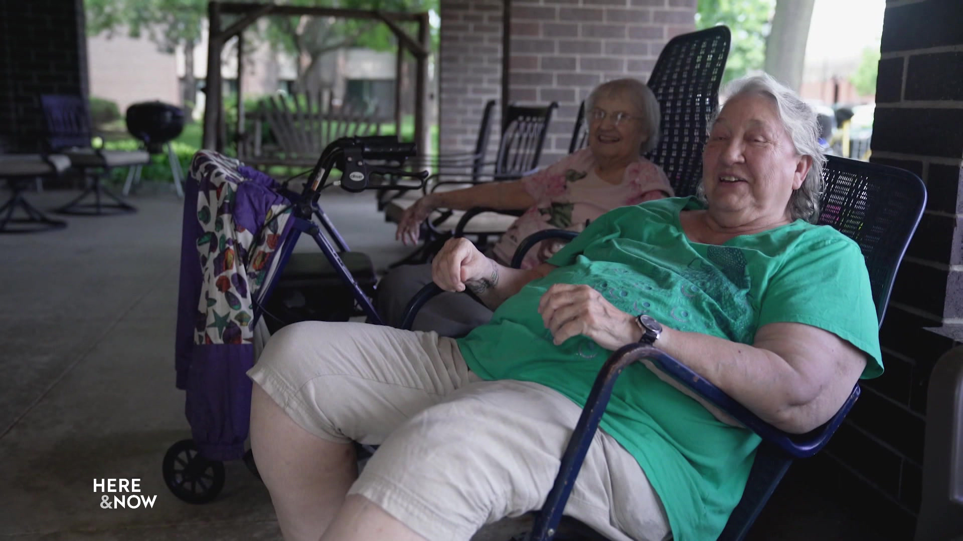Norma Tucker and another person sit on deck chairs on a covered patio.