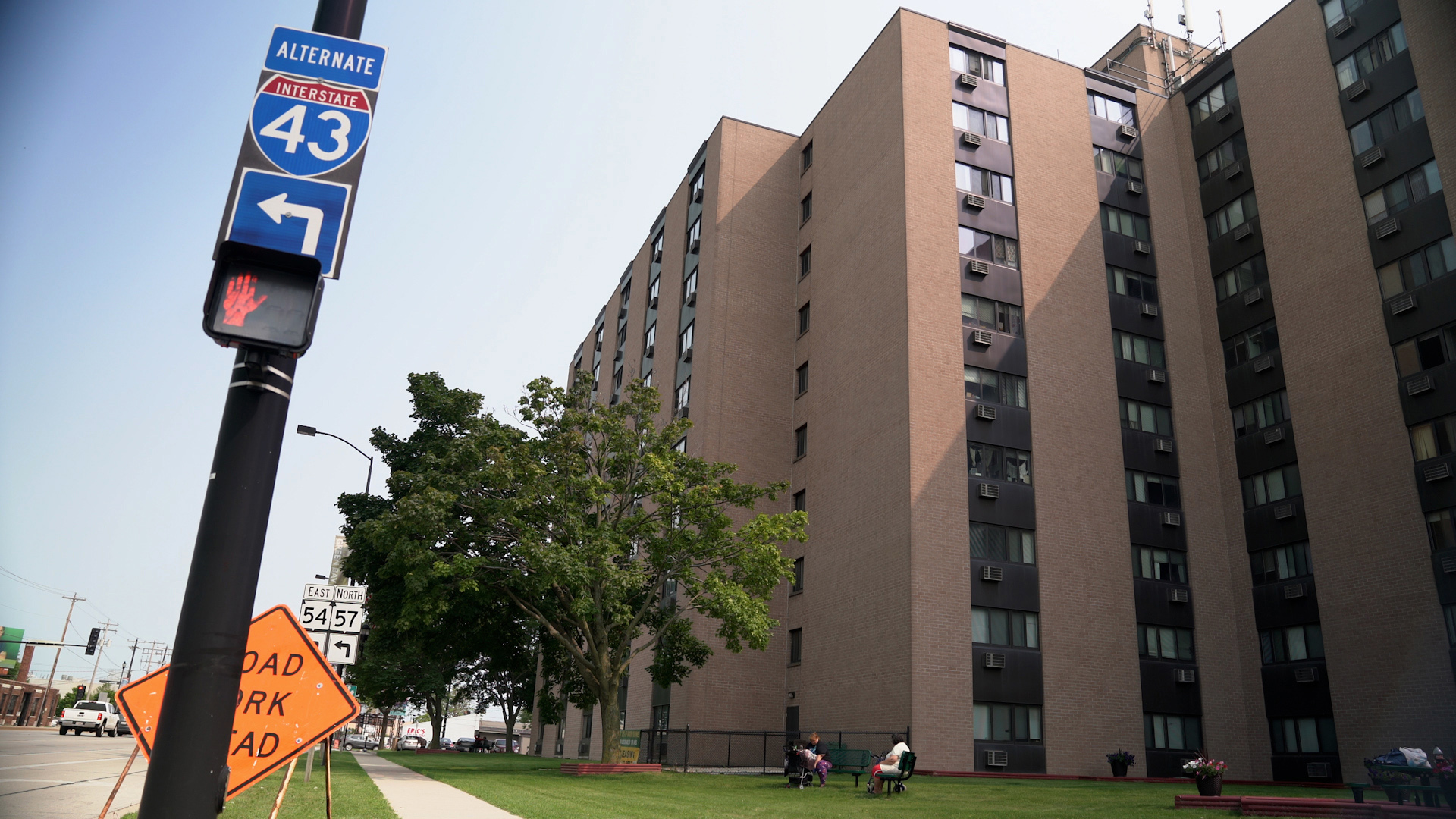 A 10-story apartment tower with Interstate 43 sign next to sidewalk