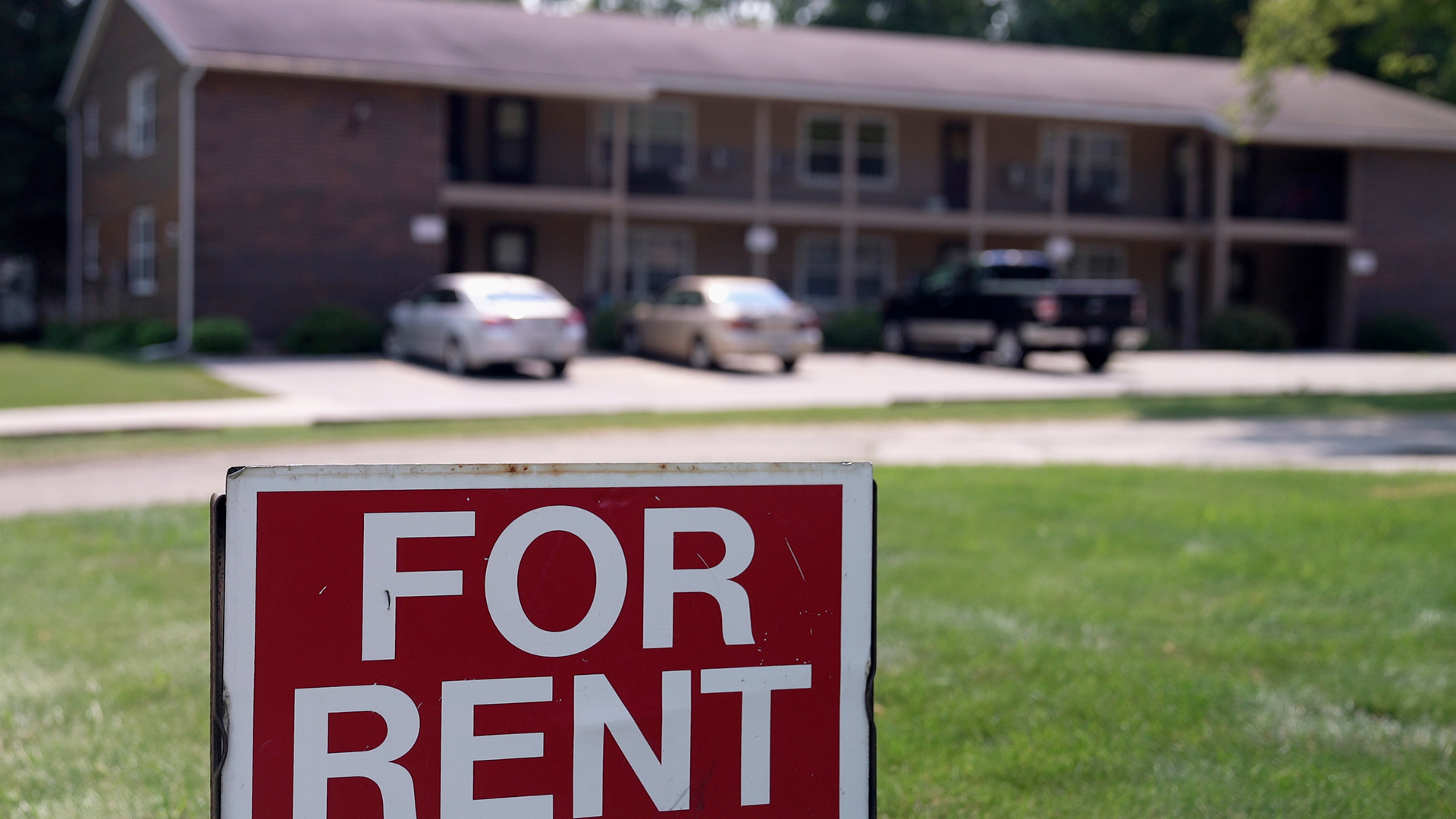 For Rent sign with apartment in background