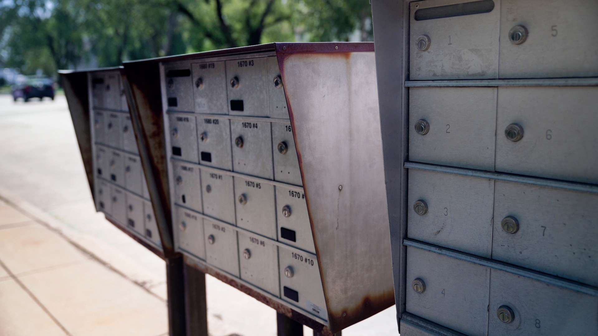 Banks of apartment mailboxes stand at a curb