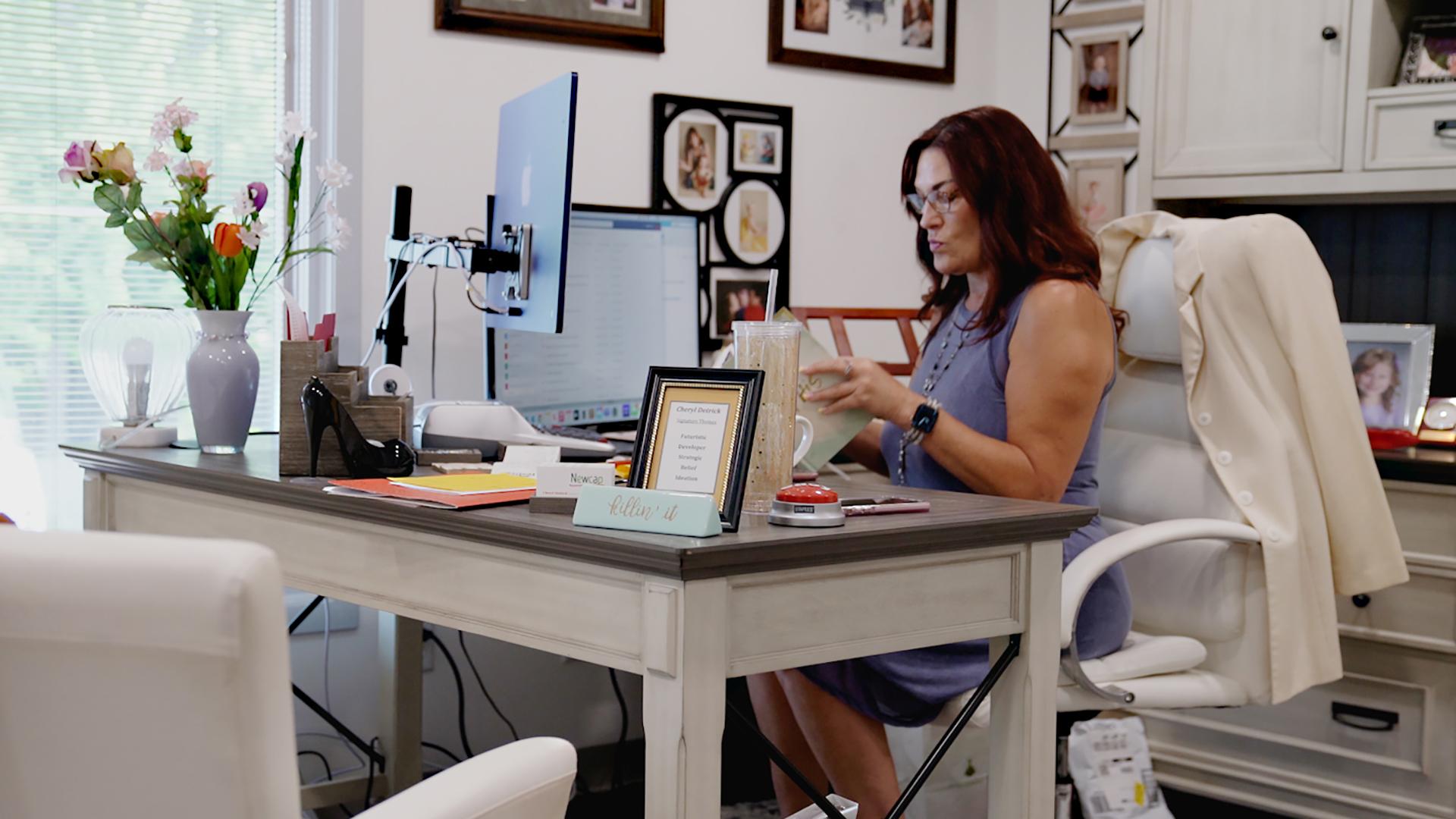 Cheryl Detrick sits a desk.