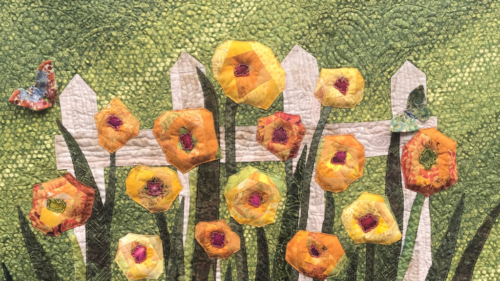 A quilt of yellow, geometric flowers against a picket fence