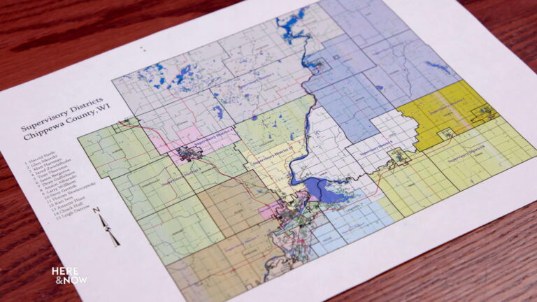 A map of Chippewa County supervisory districts sits on a table.