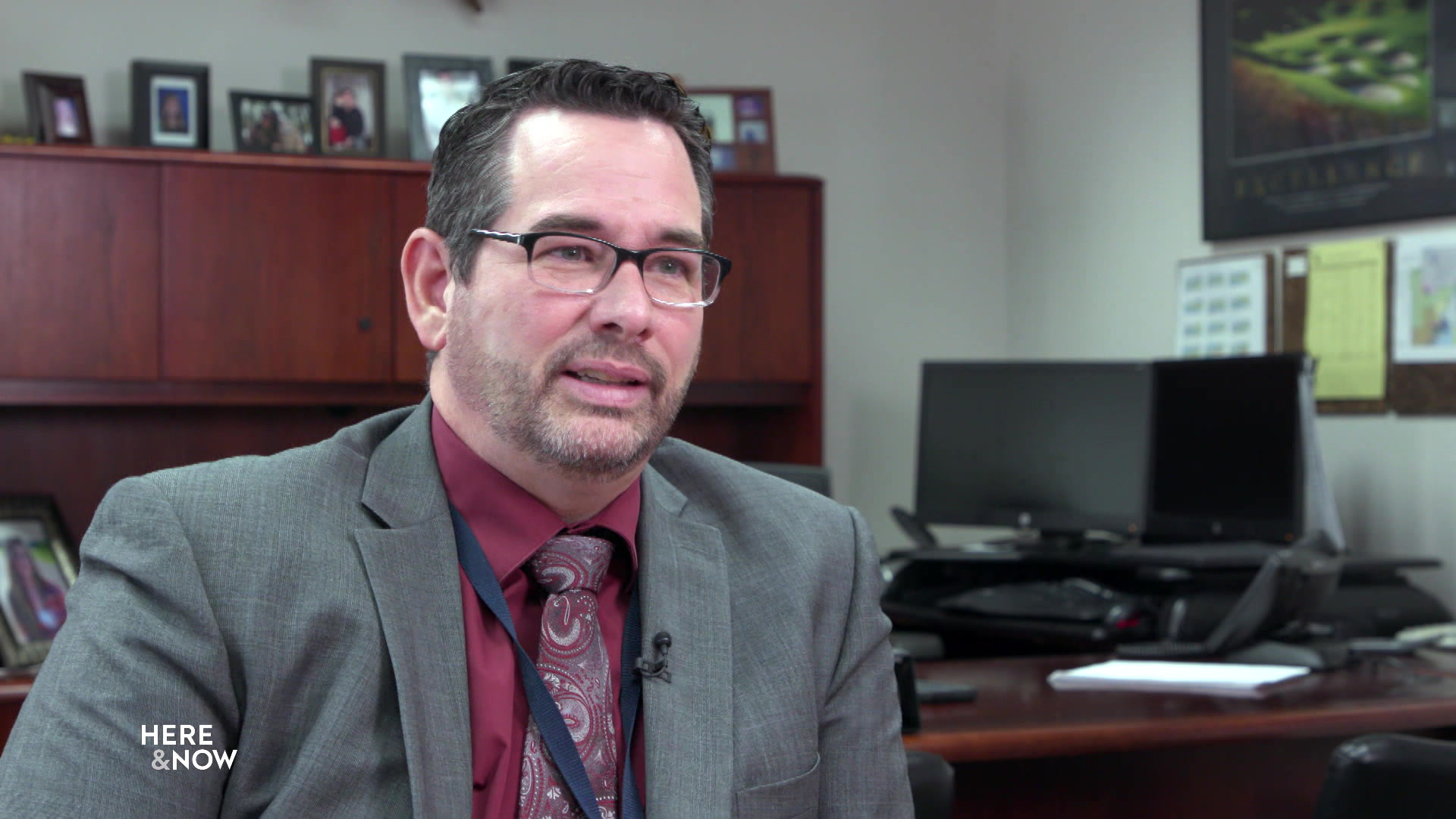 Randy Scholz sits in an office with computer and desk in background.