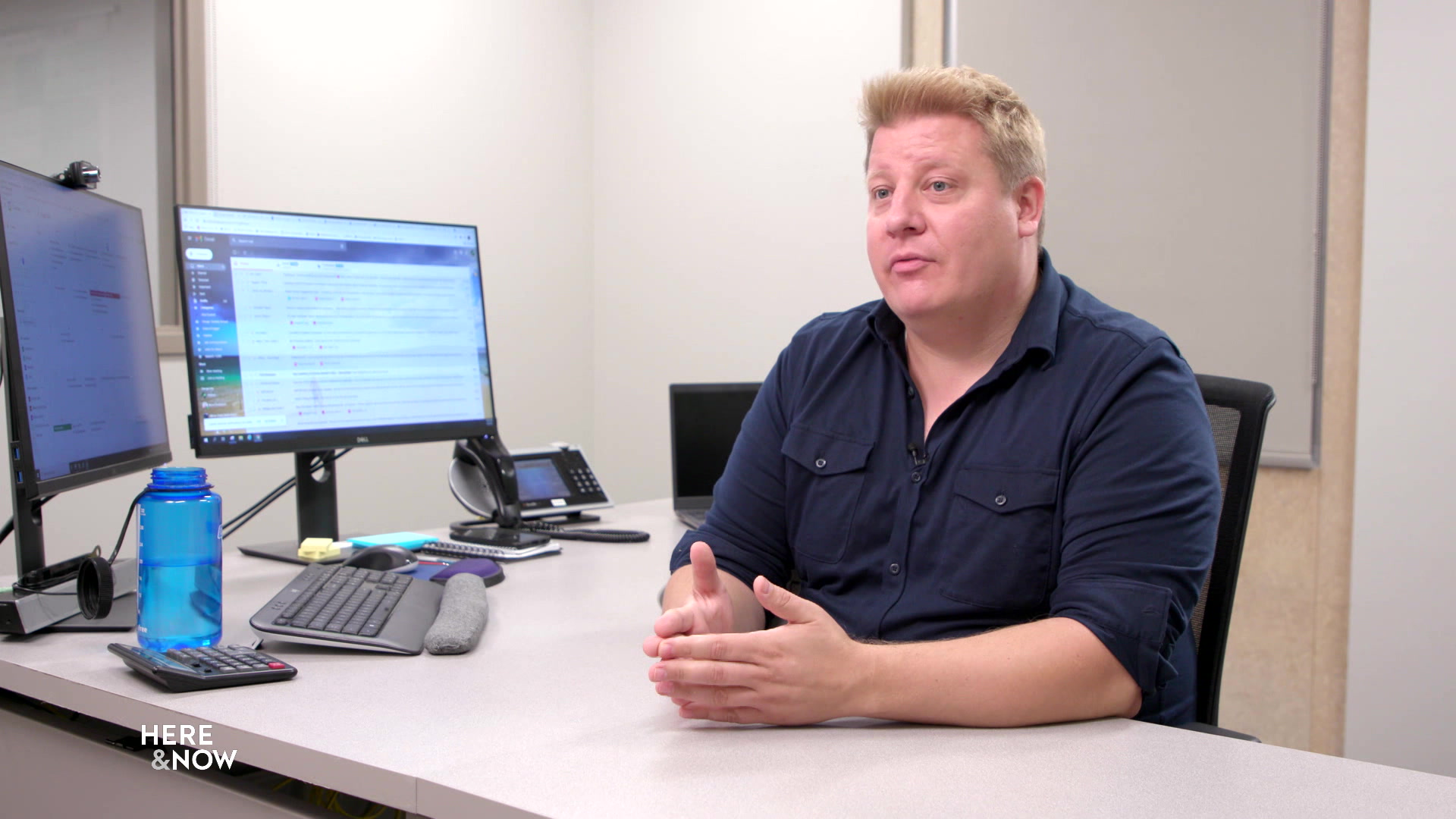 Andrew Mercil sits at a desk with two computer monitors.