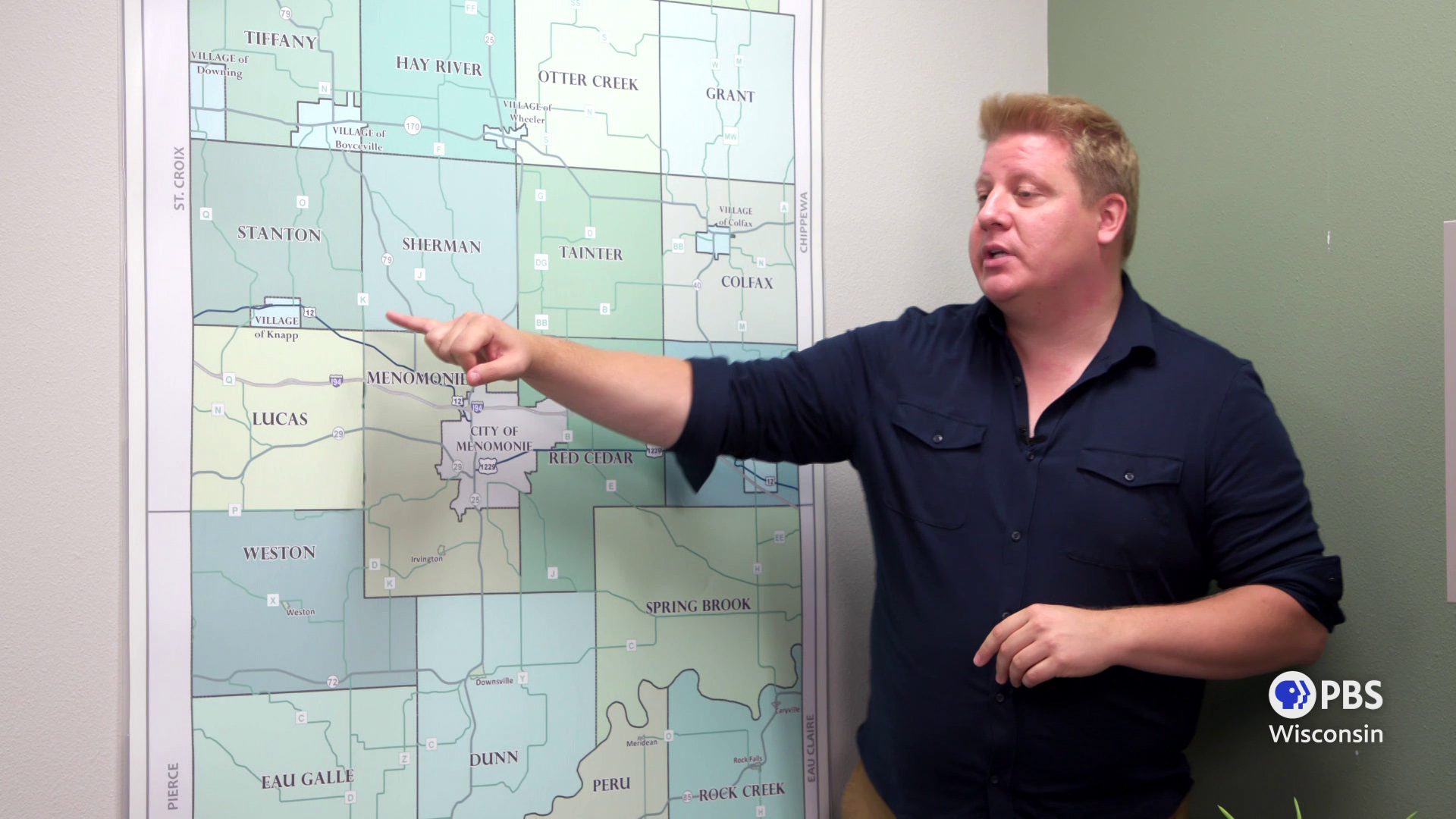 Andrew Mercil points to municipalities on a wall map of Dunn County.