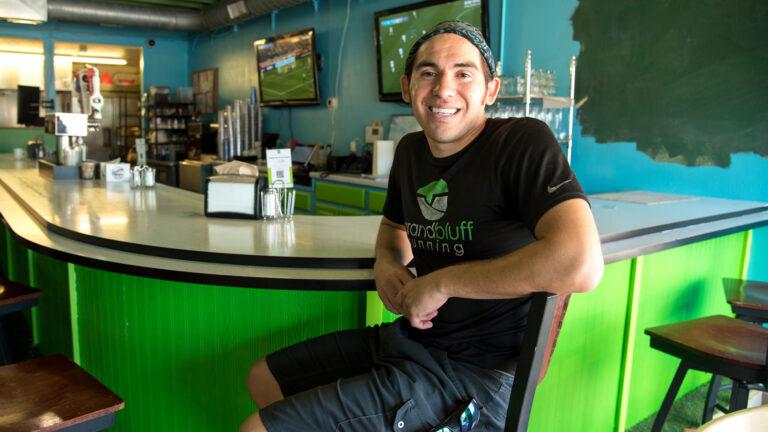Donald Greengrass Jr. sits on a chair at a restaurant counter