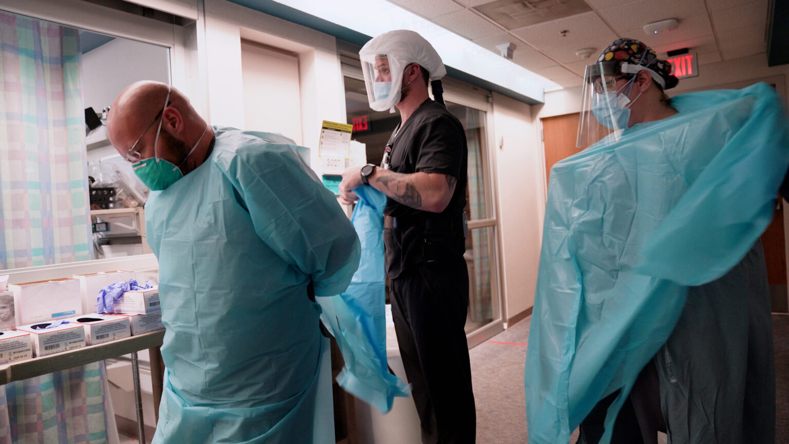 Three hospital workers put on personal protective equipment including gowns, masks and face shields in the hallway of an intensive care unit.