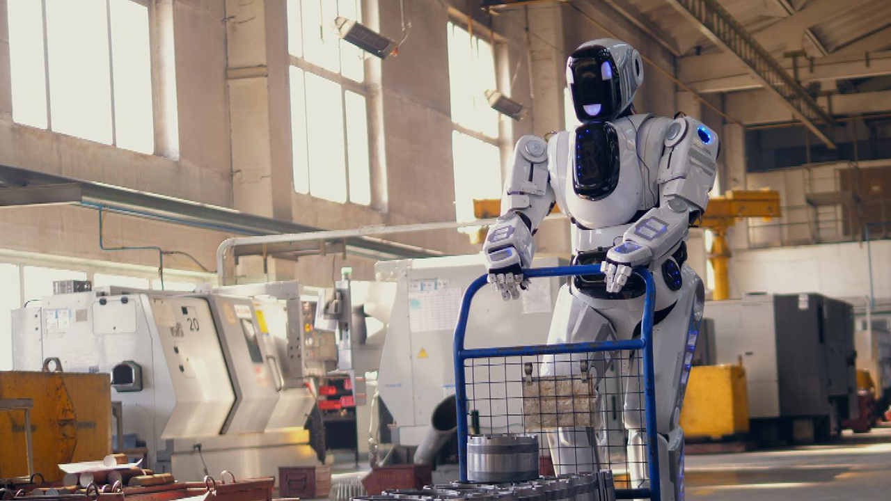 A robot pushes a cart in a factory