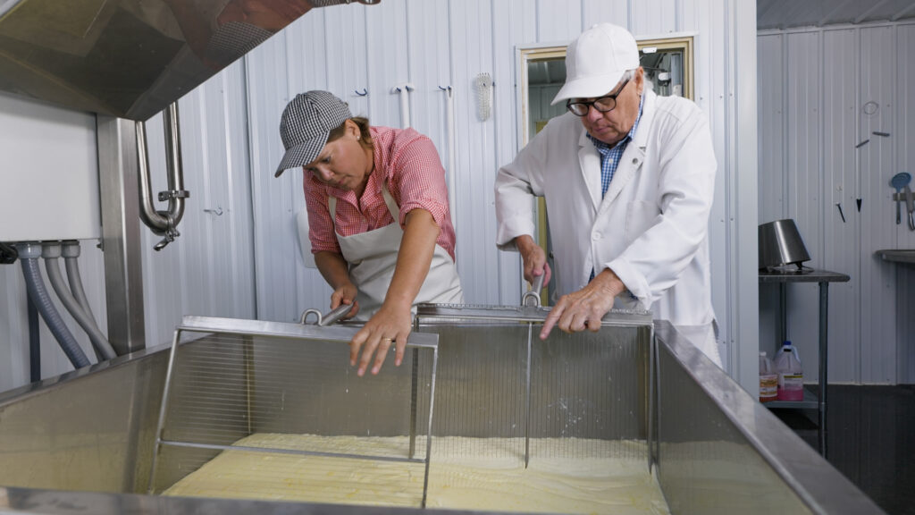 A man and woman stand by each other. They are working in a vat of cheese.